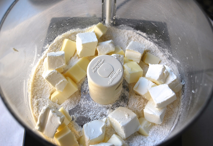 Add butter and cream cheese to flour to food processor.