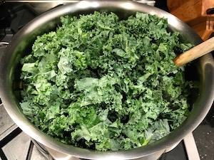 Adding kale to the pot.