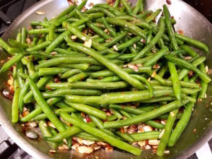 Green beans in a skillet being tossed with almonds.