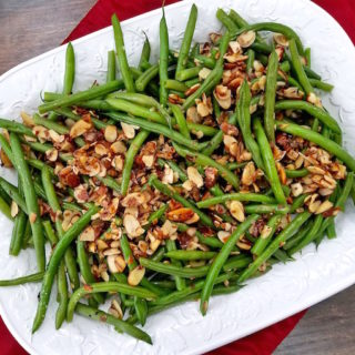 Platter of Green Beans Almondine with almonds scattered on top.