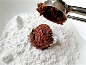 Scooping chocolate crinkle cookie dough into powdered sugar.